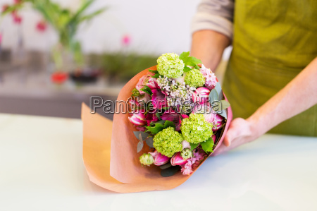 florist wrapping flowers in paper at