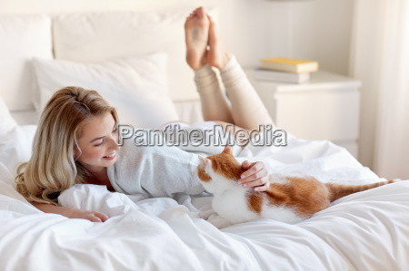 happy young woman with cat in
