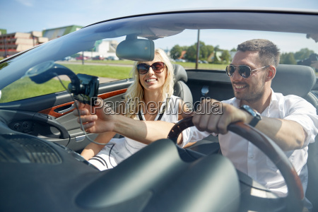 happy couple using gps navigator in