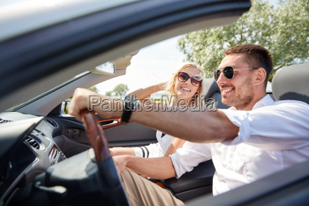 happy man and woman driving in