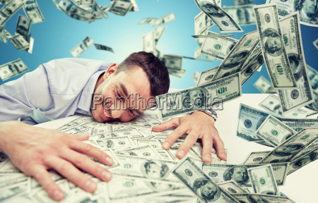 happy businessman with heap of money