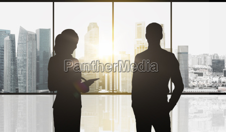 silhouettes of business partners over city