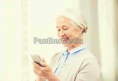 senior woman with smartphone texting at