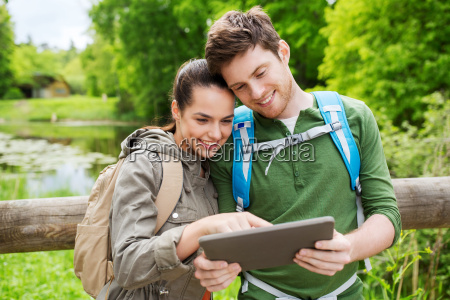 happy couple with backpacks and tablet