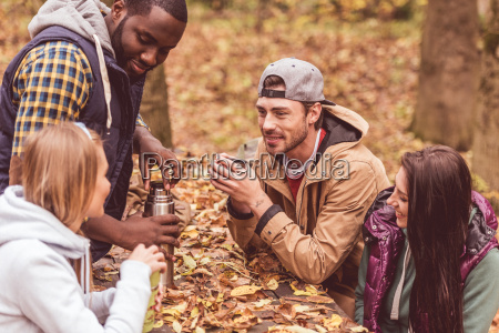 friends, pouring, hot, drink, in, forest - 20115006