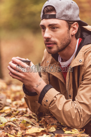 young, man, holding, cup, from, thermos - 20115002