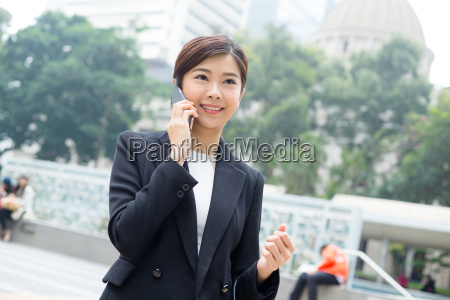 asian, businesswoman, chat, on, mobile, phone - 20116283