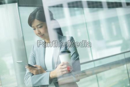 businesswoman, holding, her, smartphone - 20116025