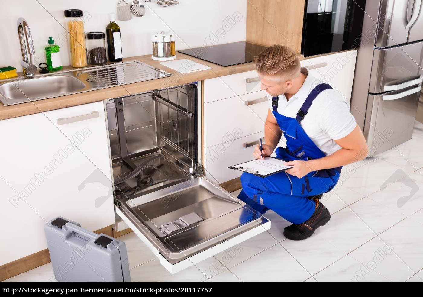 repairman, writing, on, clipboard, in, kitchen - 20117757