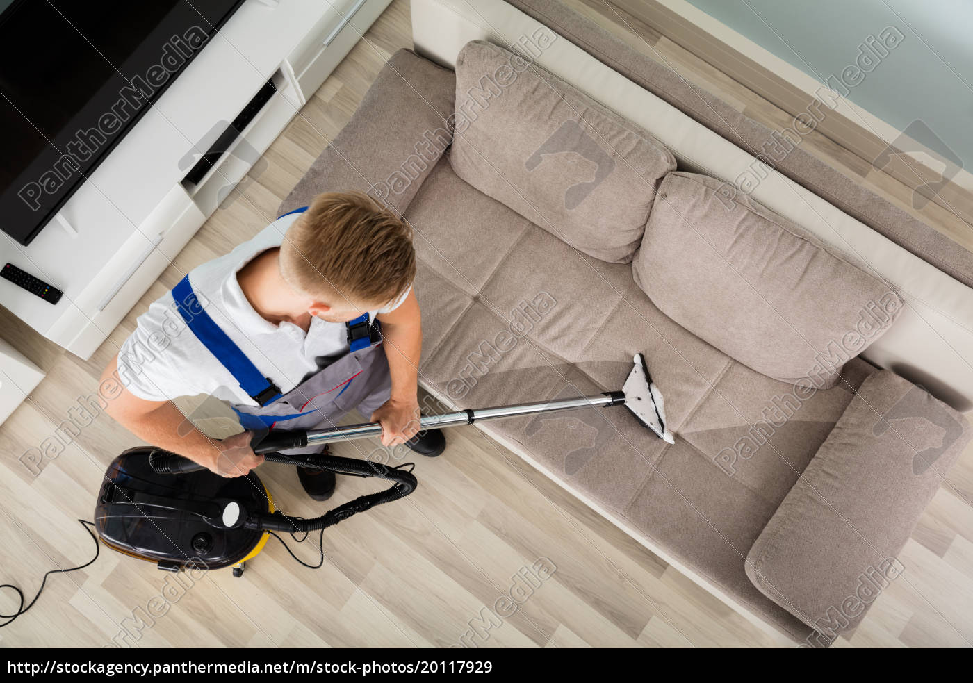 young, man, cleaner, sofa, with, vacuum - 20117929