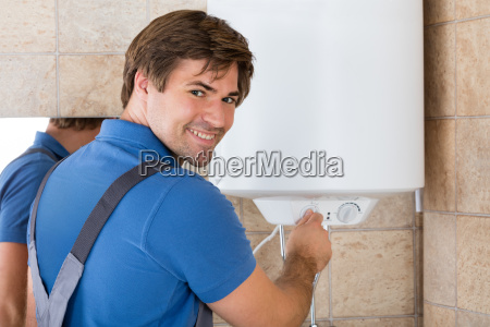 happy young repairman holding knob of