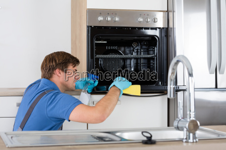 man, in, overall, cleaning, oven - 20118953