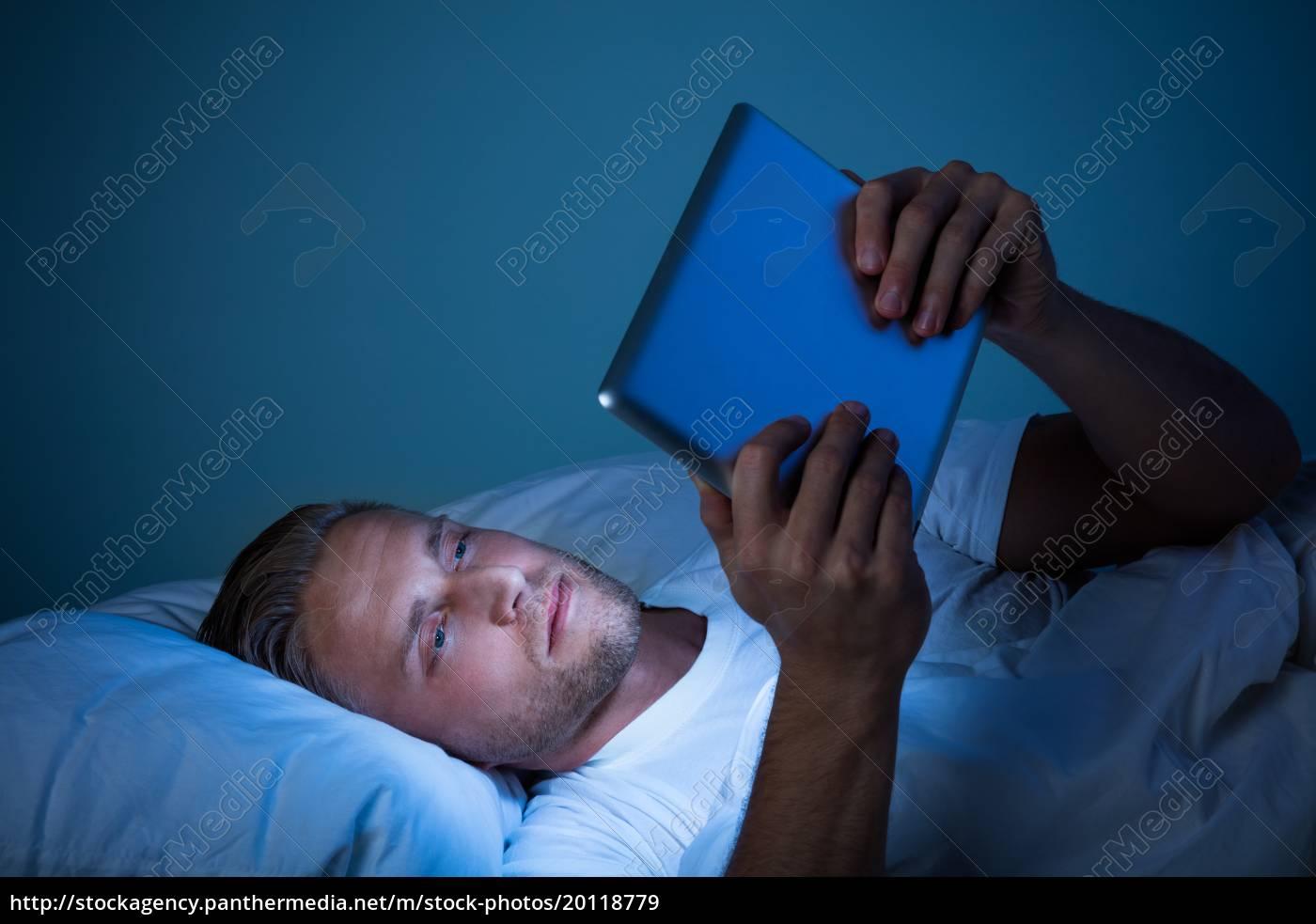man, on, bed, looking, at, digital - 20118779