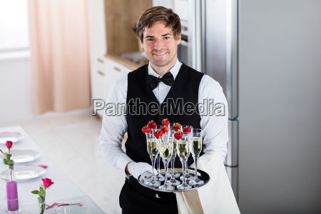 smiling, waiter, holding, tray, of, champagne - 20118933