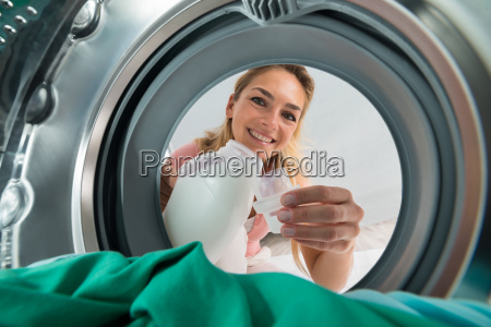 smiling, woman, pouring, detergent, in, a - 20118861