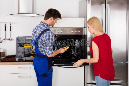 male worker repairing oven appliance using