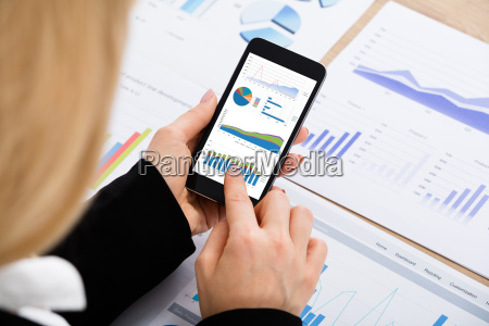 businesswoman, analyzing, graph, using, mobilephone - 20119541