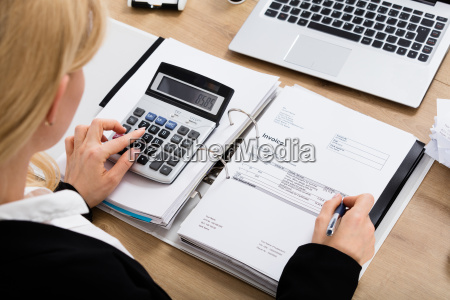 businesswoman, calculating, invoice, in, office - 20119545