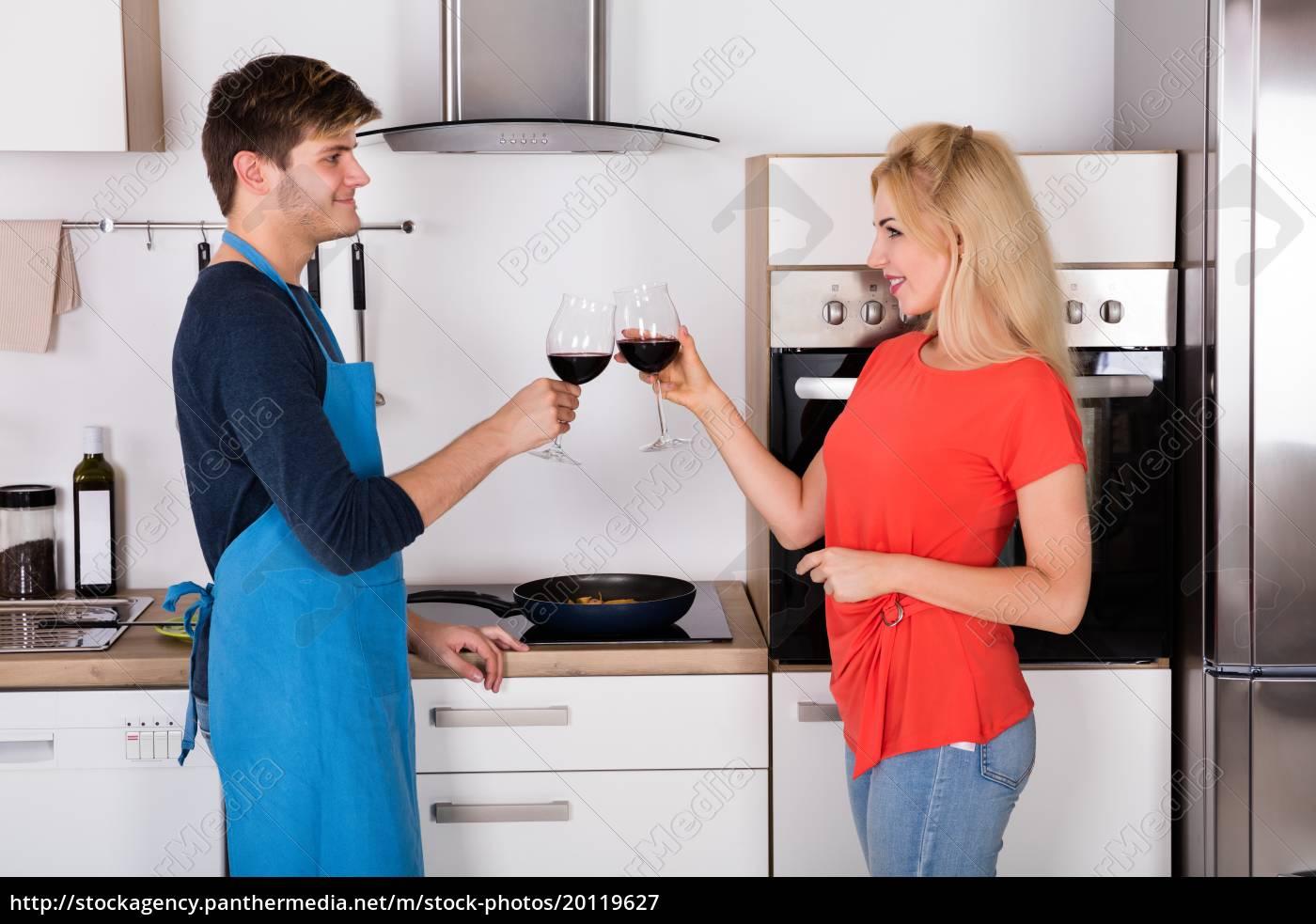 happy, couple, toasting, wine, in, kitchen - 20119627