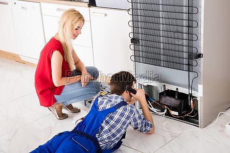 male, worker, repairing, refrigerator, in, kitchen - 20119643