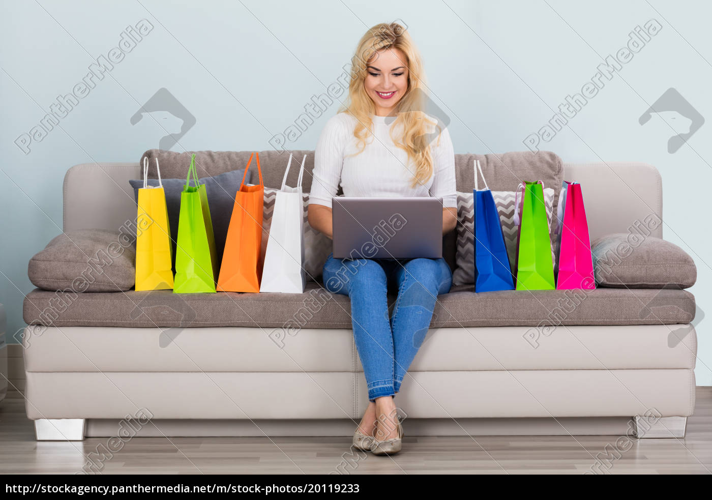 smiling, woman, using, laptop, on, couch - 20119233