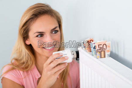 woman, adjusting, thermostat, with, bank, notes - 20119263