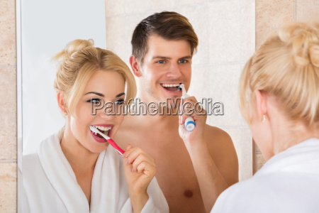 young, couple, brushing, teeth, in, bathroom - 20119729