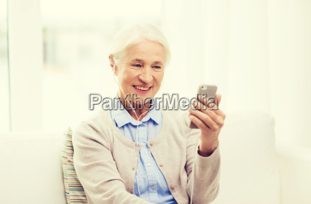 senior woman with smartphone and earphones