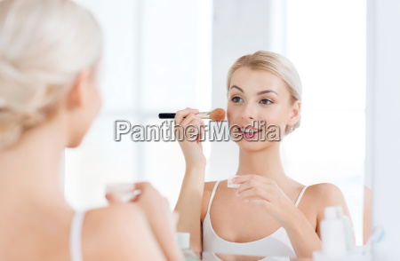 woman with makeup brush and powder