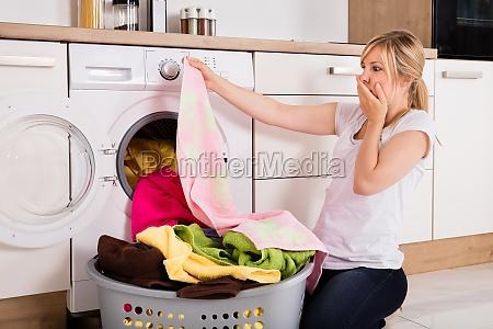 woman looking at cloth near washing