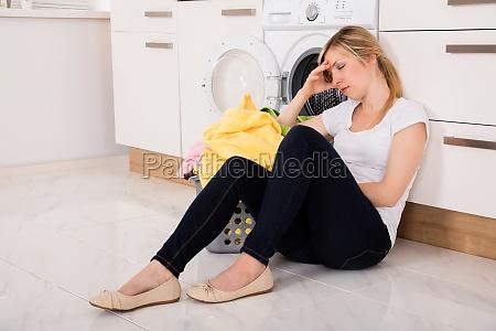 exhausted, woman, sitting, near, washing, machine - 20125559