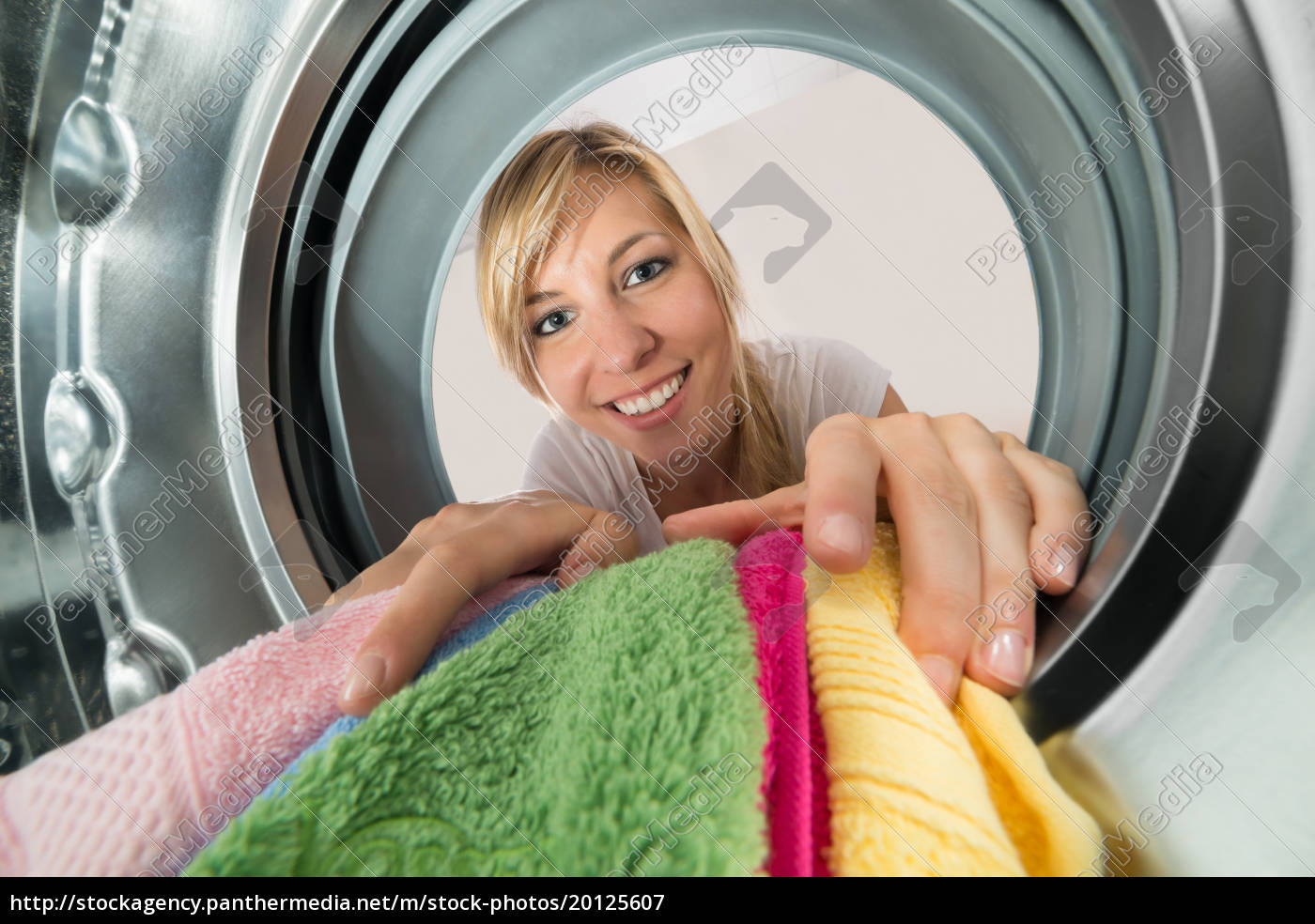 smiling, woman, inserting, clothes, in, washing - 20125607