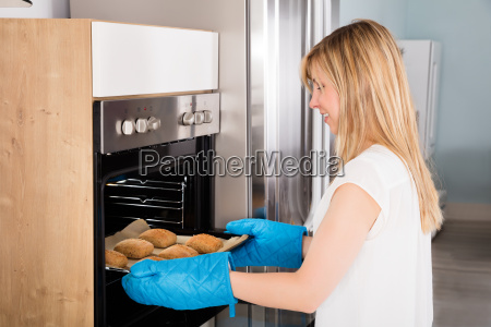 woman, taking, baking, tray, out, from - 20125485
