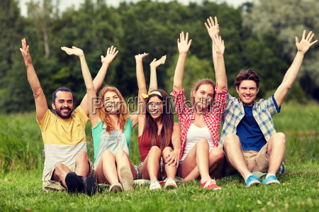 group of smiling friends waving hands