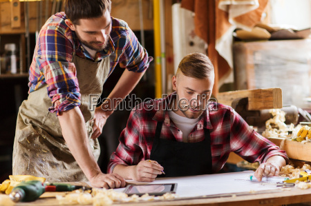 carpenters with ruler and blueprint at