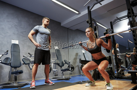 man and woman with barl flexing