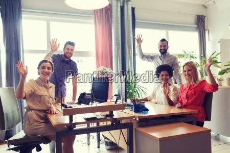 happy creative team waving hands in