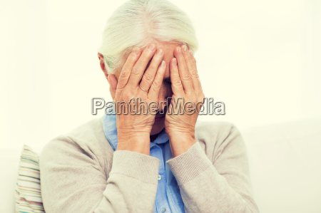 senior woman suffering from headache or