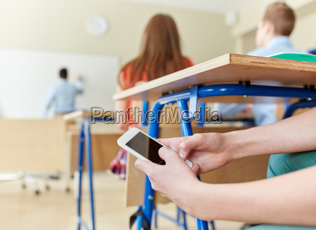 student boy with smartphone texting at