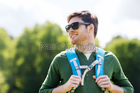 happy young man with backpack hiking