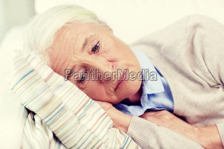 sad senior woman lying on pillow