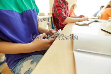 student girl with smartphone texting at