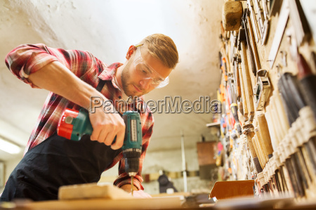 carpenter with drill drilling plank at