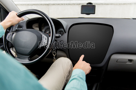 man driving car and pointing to