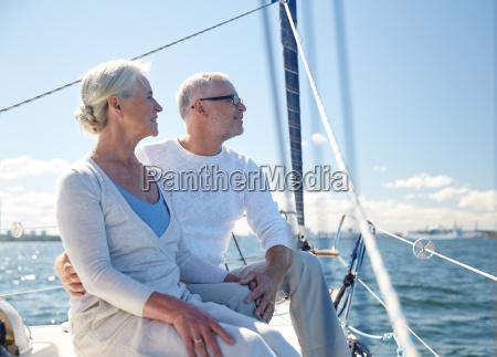 senior couple hugging on sail boat