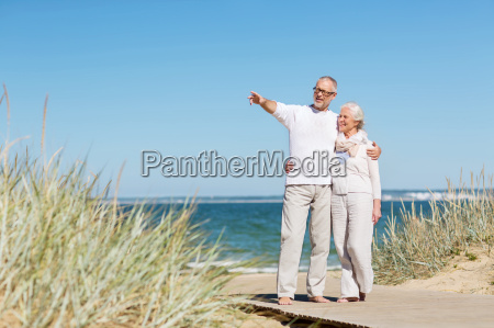 happy senior couple hugging on summer