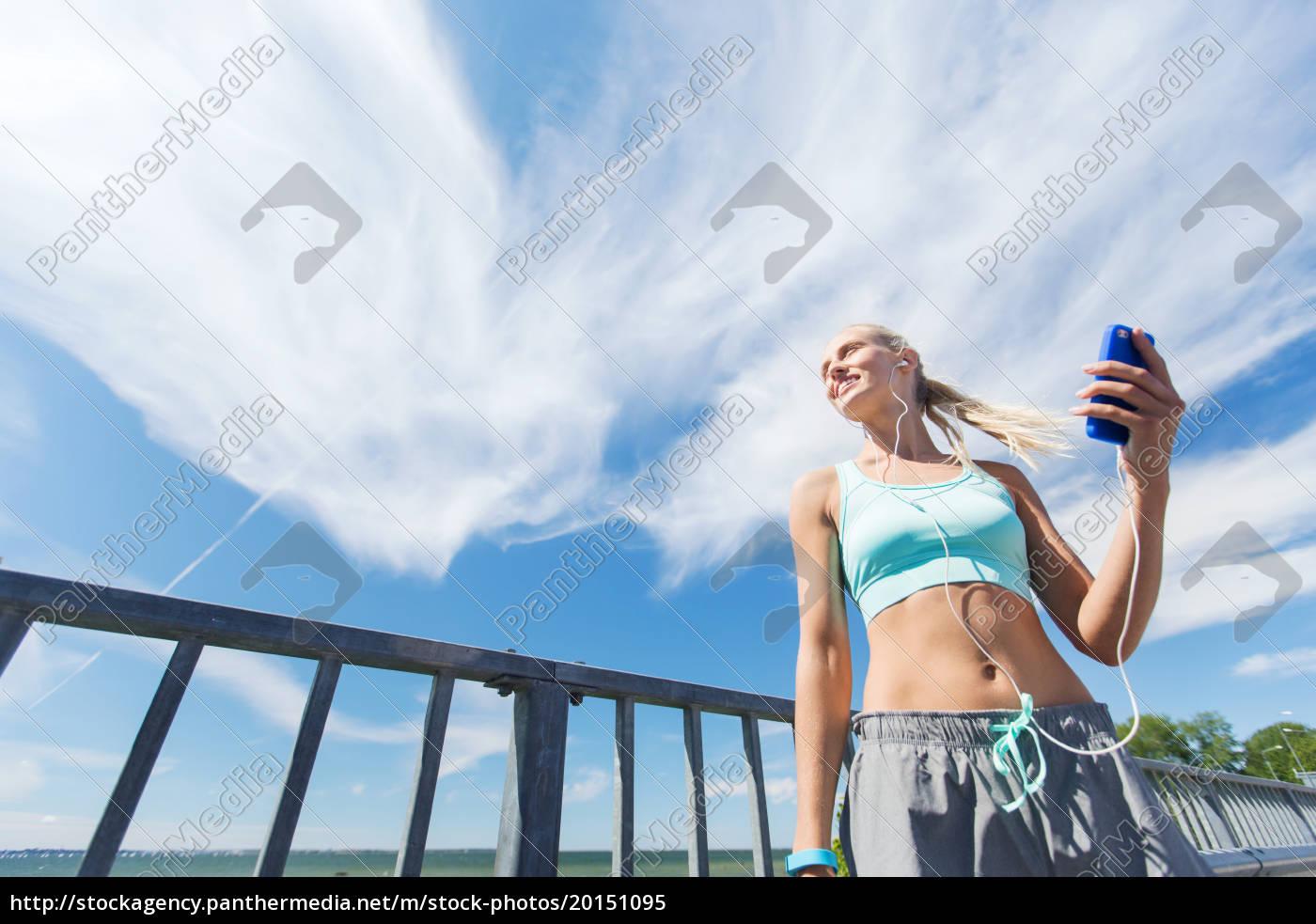 happy, woman, with, smartphone, and, earphones - 20151095