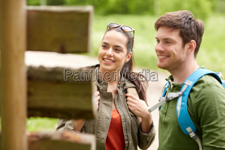 smiling couple at signpost with backpacks