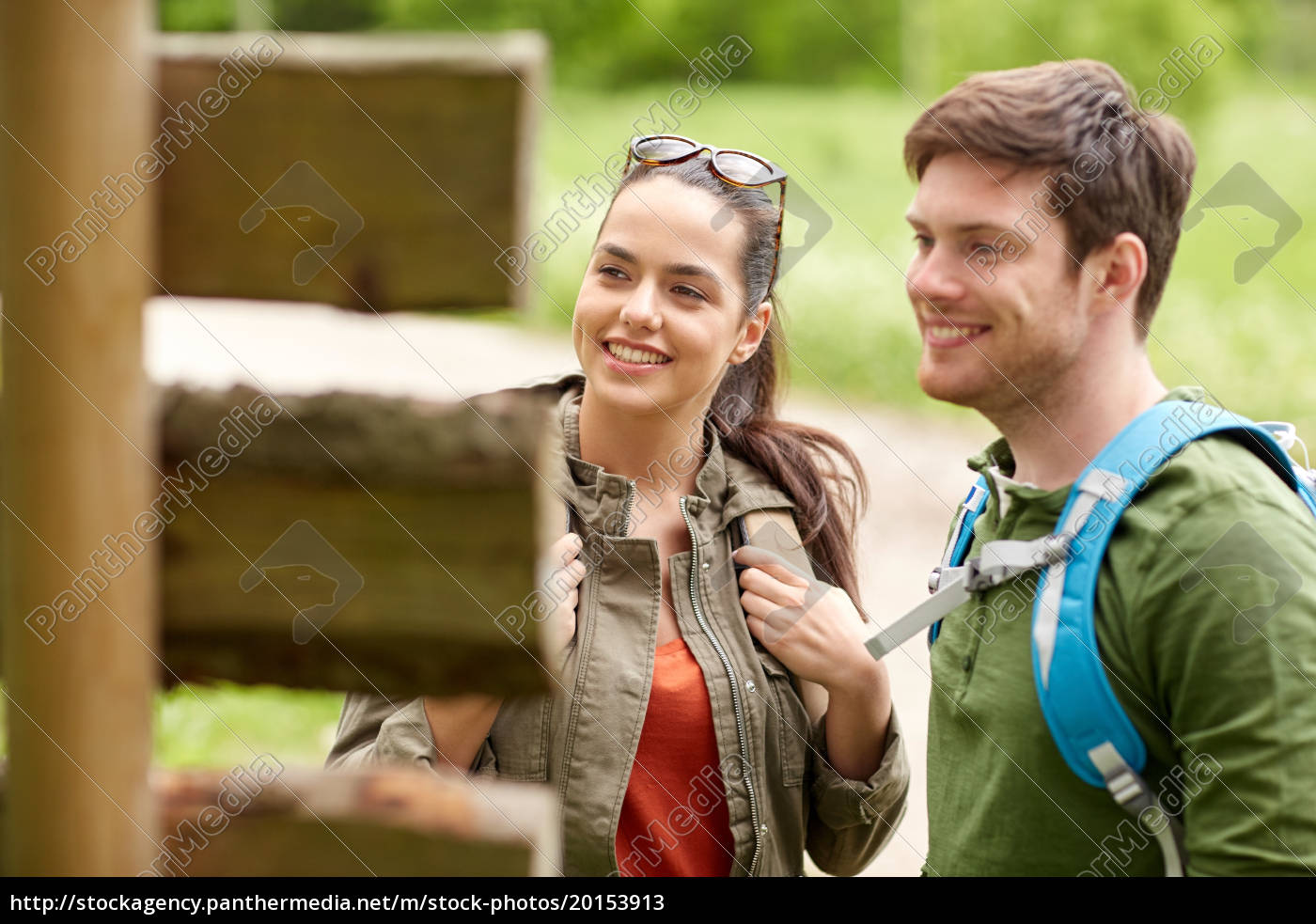 smiling, couple, at, signpost, with, backpacks - 20153913
