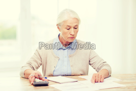senior, woman, with, papers, and, calculator - 20154711